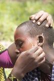 Girl having face painted,  Maasi Village, Ngorongoro Conservatio Stock Photos