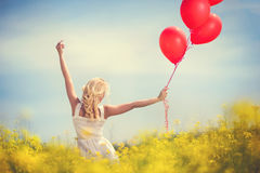 Girl having fun with balloons in meadow of flowers Royalty Free Stock Photography