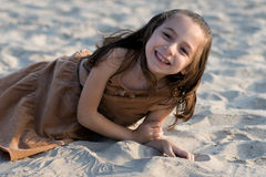 Girl having fun at beach. Smiling young girl lying down on sand at beach Stock Photography