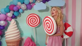 Girl having fun with big plastic candy in Studio. Funny girl in pink dress having fun with big plastic candy or Lollipop in the Studio, she pretends to sing stock footage