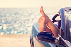 Girl having fun in blue cabriolet against toned sky background. Summer vacation and travel concept Stock Image