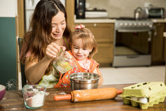 Girl having fun cooking with her mother Royalty Free Stock Photos