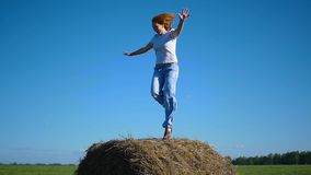 Girl having fun dancing in a haystack stock video