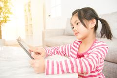 Girl having fun enjoy using digital tablet. Beautiful kids girl having fun enjoy using digital tablet mobile pad at desk in the living room at home. family Royalty Free Stock Photos