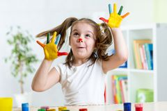 Girl having fun, her face and palms covered with. Child girl having fun, her face and palms covered with paint stock photo