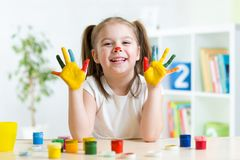 Girl having fun, her palms covered with paint Royalty Free Stock Photo