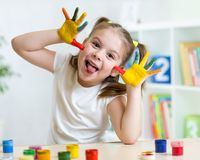 Girl having fun, her palms covered with paint. Kid girl having fun, her palms covered with paint royalty free stock image