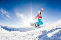 Girl having fun on her snowboard. Jumping Royalty Free Stock Image