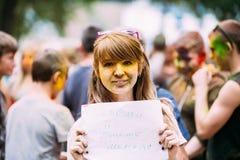 Girl having fun at Holi color festival in park in Stock Image