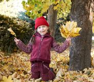 Girl having fun an make faces in autumn forest, yellow leaves and trees on background Royalty Free Stock Photography