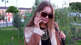 Girl having fun outdoors calling smart phone, stock video