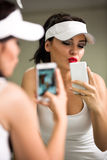 Girl having fun with a phone in front of the mirror Stock Photos