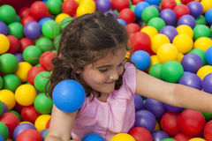 Girl having fun playing in a colorful plastic ball pool Royalty Free Stock Image