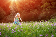 Girl having fun playing outdoors during sunny summer afternoon Stock Photos