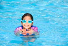 Girl having fun playing in swimming pool Stock Images