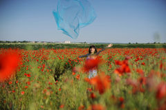 Girl having fun in poppies with blue cloth Stock Image