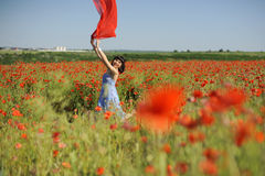 Girl having fun in poppies with red cloth Royalty Free Stock Images