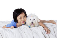 Girl having fun with puppy on bed. Lovely little girl smiling happy while looking at the camera with her dog on bed, isolated on white background Stock Photography