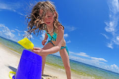 Girl Having fun in sand. Young girl having fun building sand castle on beach royalty free stock image