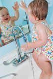 Girl having fun in sink. One year old toddler girl having fun while cooling off in a sink in a home or public bathroom or restroom on a hot summer day stock image