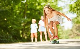Girl is having fun while skateboarding. Smiling girl is having fun while skateboarding in the vacation royalty free stock images
