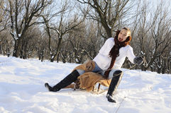 Girl having fun on sledge. Young joyful woman smiling in winter season Stock Image