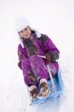 Girl having fun in snow. Beautiful girl having fun in snow with sledge Stock Photo