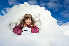 Girl having fun in snow cave at winter day Royalty Free Stock Photo