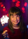 Girl Having Fun with Sparkler. Young smiling happy girl having fun with sparkler before coloured lights background Stock Photography