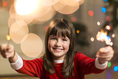 Girl Having Fun with Sparkler. Young smiling happy girl having fun with sparkler before coloured lights background Stock Photo