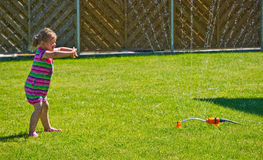 Girl having fun with sprinkler in garden Royalty Free Stock Photography