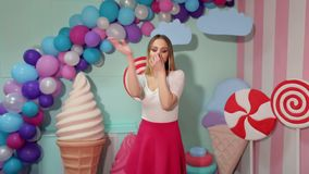 Girl having fun in the Studio with huge sweets. Portrait of a cheerful dancing girl in a pink skirt and white blouse on the background of the interior with big stock footage