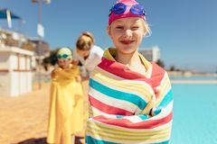 Girl having fun swimming learning session. Girl wrapped in towel winking an eye standing by the pool. Girl standing by the pool with coach wrapping boy in towel royalty free stock image