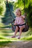 Girl having fun on a swing. Cute one year old girl having fun on a swing Royalty Free Stock Images