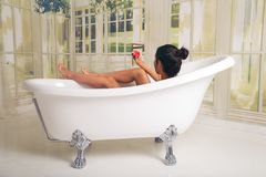 Girl having fun in the tub. She is in a spacious and elegant bathroom.  stock photography
