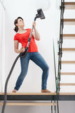 Girl having fun during vacuuming floor Stock Photos