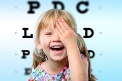 Girl having fun at vision test. Royalty Free Stock Images