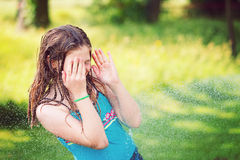 Girl having fun outdoor with water Stock Image