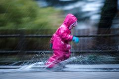 Girl is having fun in water on street in cold autumn day, girls splashing water in rain. Happy and cheerful girl enjoying cold weather, kid in pink rain coats stock images