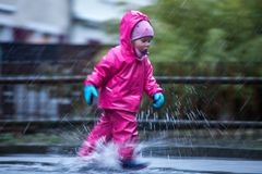 Girl is having fun in water on street in cold autumn day, girls splashing water in rain. Happy and cheerful girl enjoying cold weather, kid in pink rain coats stock photos