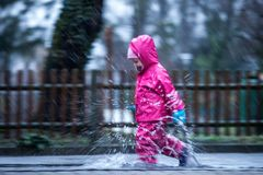Girl is having fun in water on street in cold autumn day, girls splashing water in rain. Happy and cheerful girl enjoying cold weather, kid in pink rain coats stock photo