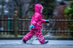 Girl is having fun in water on street in cold autumn day, girls splashing water in rain. Happy and cheerful girl enjoying cold weather, kid in pink rain coats royalty free stock photos