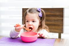 Girl Having Healthy Food At Home. Innocent girl looking away while eating food with spoon at home royalty free stock images