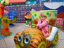 Girl having joy. Little girl on a mini merry-go-round, having fun Royalty Free Stock Image
