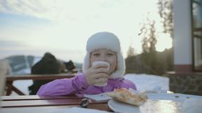 The girl is having lunch. Happy girl in the middle of snowy mountains. Winter holidays. stock footage
