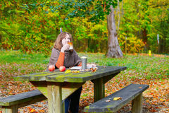 Girl having a picnic in park on a fall day Royalty Free Stock Photography
