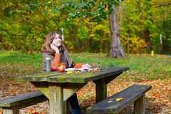 Girl having a picnic in park on a fall day Stock Photo