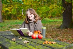Girl having a picnic in park on a fall day Stock Photos
