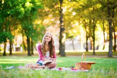 Girl having a picnic and writing in her diary Stock Image
