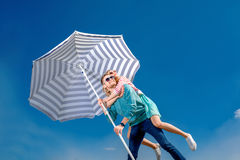 Girl having piggy back ride on a man with beach umbrella on blue Stock Photos